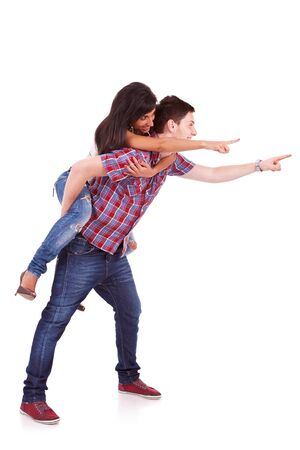 piggy back: Side view of a young man carrying his girlfriend on his back with their hands pointing towards something