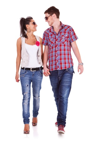 Casual couple is walking towards the camera looking at each other, on white