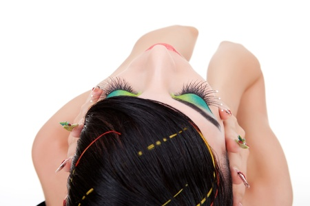 Close up of a brunette young woman holding her palms on her face and her eyes shut. Top view of a young woman model with exotic make-up and nails. photo
