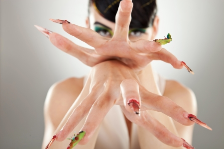 Young woman model holding one hand above another emphasising beautiful fingernails, against gray background. photo