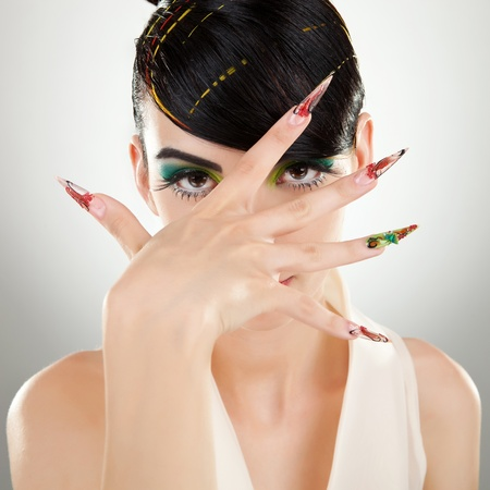 Young woman with modern hairstyle, brightly makeup and big nails covering her face with her hand. on gray background photo