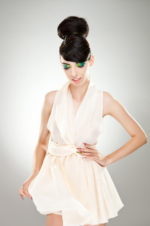 Portrait of a young woman holding her cute white dress and one hand on her waist, while looking down photo