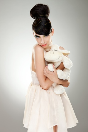 appealing young woman model in white dress hugging her fluffy sheep toy, on gray background photo