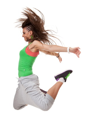 knees bent: Side view of a modern woman dancer with a funky hairdo jumping with knees bent and hands back
