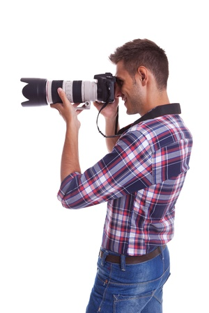 photographer: Side view of a young photographer taking a photo. Isolated on white Stock Photo