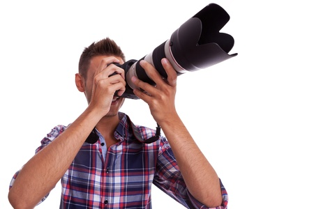 photography session: Young photographer holding a professional DSLR camera and taking pictures  Stock Photo