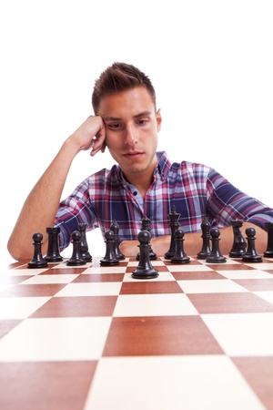 pawn adult: Young casual man thinking in front of the chessboard, isolated on white Stock Photo