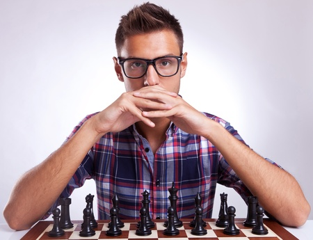 the next life: Portrait of a young man waiting for your move. Chess oponent looking provocatively into your eyes.