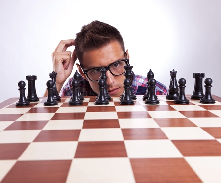 pawn adult: Young casual eyeglassed man in front of his first chess move. Over gray background.