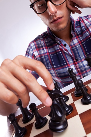 pawn adult: A young casual man moving his chess piece for his next move. on gray background