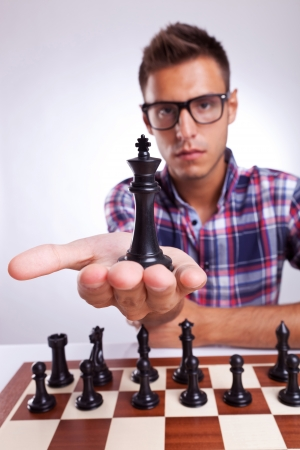 chess player: young man chess player with eyeglasses holding up his king, on gray background
