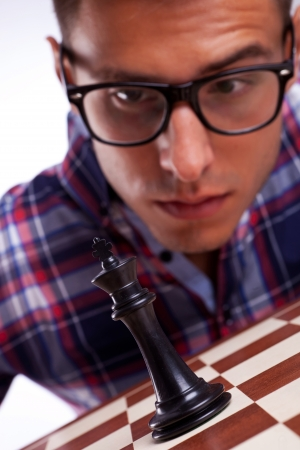 concentrating: Young chess player looking at his king