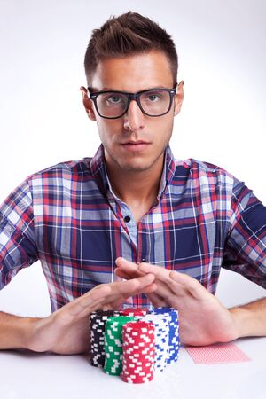 all in: young poker player with eyeglasses going all in, on gray background