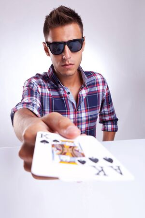 Portrait of young man showing poker pair of king and ace of clubs on gray background  photo