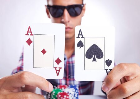 young poker player showing a pair of aces, one of diamonds and the ohter of clubs photo