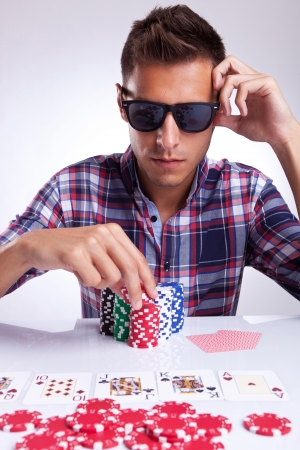 young poker player with sunglasses preparing to raise the bet photo