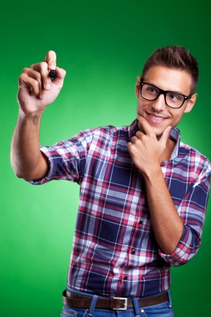 pensamiento creativo: Casual hombre joven escribir con marcador sobre fondo verde