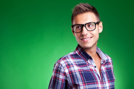Attractive young casual man wearing glasses and looking away, against green background Stock Photo - 15025103