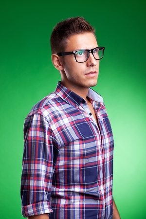 looking away from camera: Young man model posin in a squared shirt, looking away from camera. On green background
