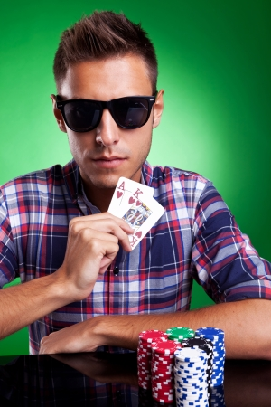 Young poker player showing ace and king  of hearts on green background photo