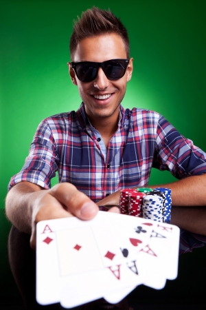 Young casual man showing his poker hand. Four of a kind. On green background photo