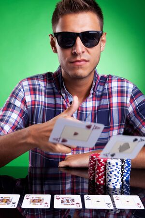 Young casual poker player wearing sunglasses, throwing a pair of aces over green background