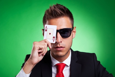 Young business man with sunglasses covers one eye with an ace of hearts. Over green background. photo