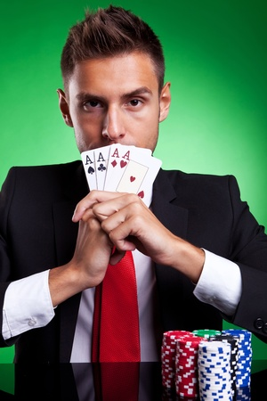 card player: Young businessman card player covering his mouth with four aces, on green background Stock Photo