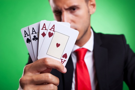 four of a kind: Picture of a young business man showing a four of a kind hand of aces, on green