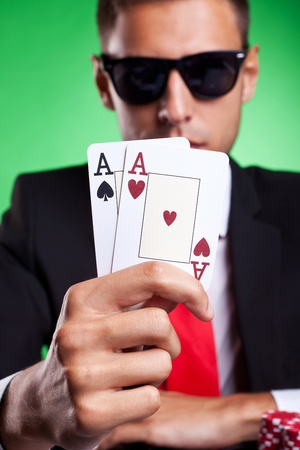Young business man showing you his pair of aces, on green background photo