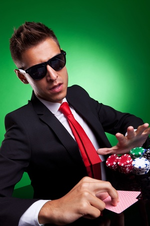 Confident young business man going all in, over green background photo