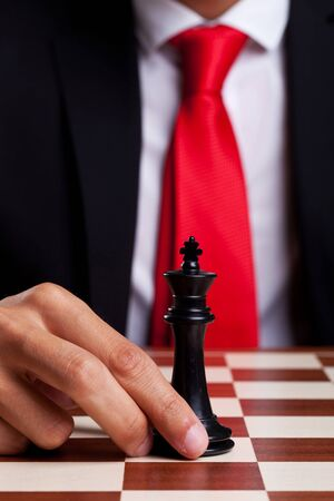 Business man moving his only king left on the board Stock Photo - 15024268