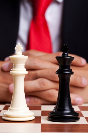 Pair of black and white chess kings in front of businessman photo