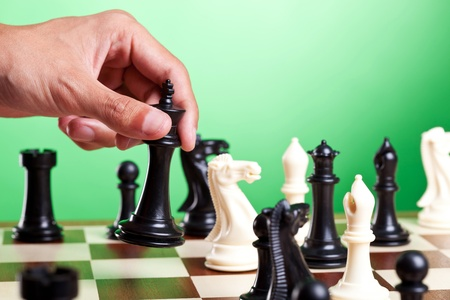 Human hand moves king on chessboard. Green background Stock Photo
