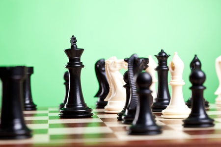 strong strategy: Chess pieces on board. Focus on the black king. Green background.