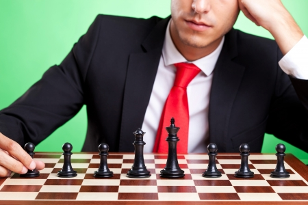 battles: Young business man standing in front of chess line-up. On green background