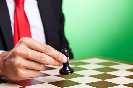 business man moving a pawn, over green background photo