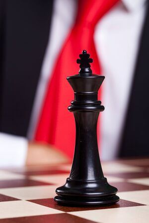 close-up picture of a black chess king alone on the chessboard with a businessman in the back Stock Photo - 15024256
