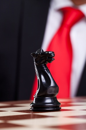 close-up picture of a black chess knight alone on the chessboard with a suit in the back photo