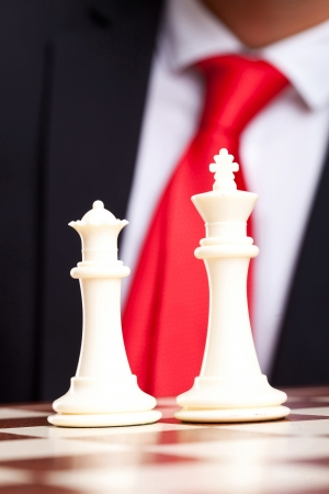 White chess king and queen in front of business man in suit photo