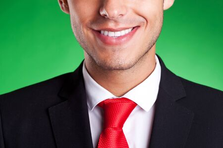 cropped image of a young business man smiling, over green background photo