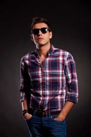squared: Casual young man standing with both hands in pockets. He is wearing sunglasses and a squared shirt and has a cocky attitude look. On dark background