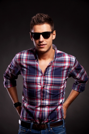 waistup: Waist-up picture of a young casual model wearing sunglasses and a squared shirt, facing the camera over dark background