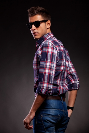 back to camera: Back view of a hot young casual man with shades, looking at the camera. On dark background