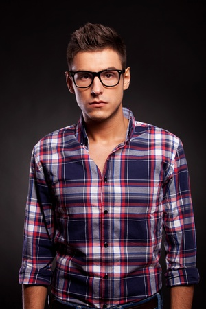 Picture of a young casual eyeglassed man looking very seriously at the camera, against black background Stock Photo - 15025136