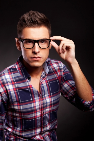 serious young casual man putting on his sunglasses, presenting them, over black background photo