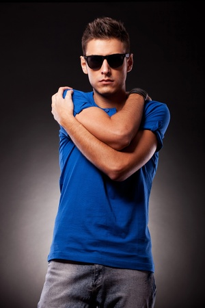 waistup: Waist-up picture of a young casual man with sunglasses holding his hands folded with elbows in front and palms on his shoulders, while facing the camera
