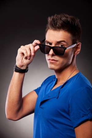 eyebrow raised: side view of o young casual man lowering his sunglasses and looking at the camera with an eyebrow raised