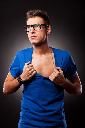 ripping shirt: Portrait of a casual young man with eyeglasses ripping his blue shirt while looking away from camera, on black background