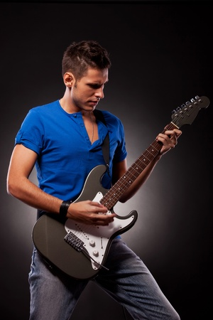 Shot of a young man playing his guitar with great emotions.  photo